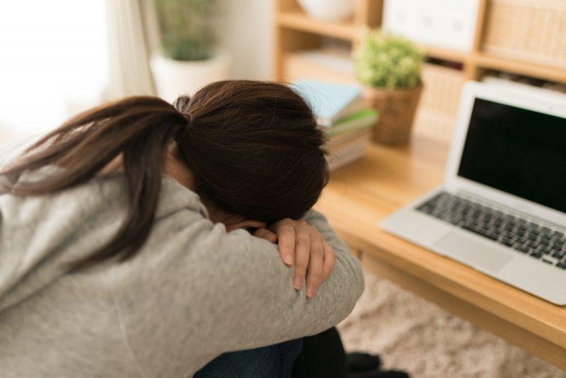 辛い生理痛で苦しそうな女性の後ろ姿
